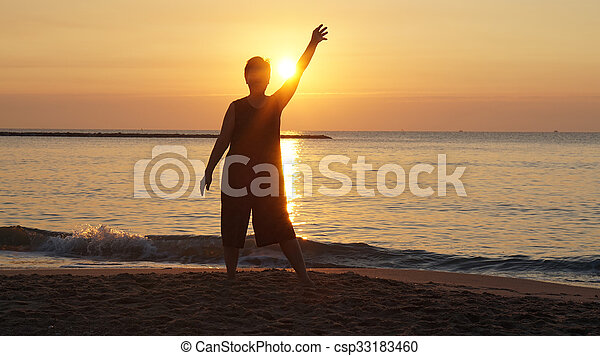 senior woman silhouette raising hand in front of new day ornage sunrise by the ocean - csp33183460