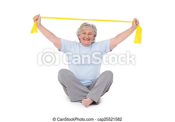 Senior woman using resistance band - csp25521582