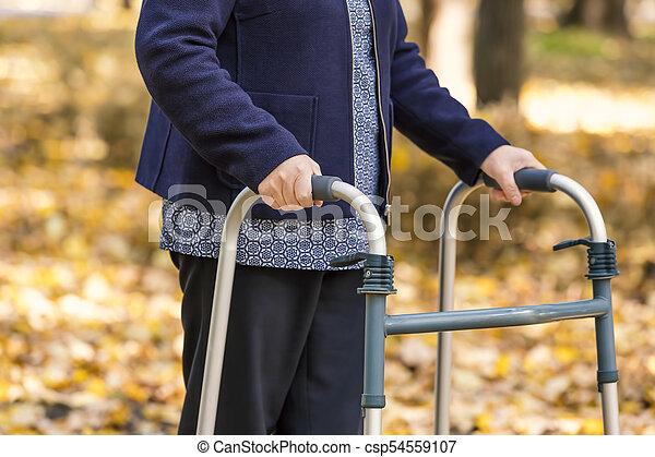 Senior woman walking with walker in autumn park - csp54559107