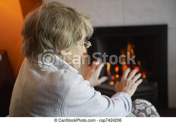 Senior Woman Warming Hands By Fire At Home - csp7424206