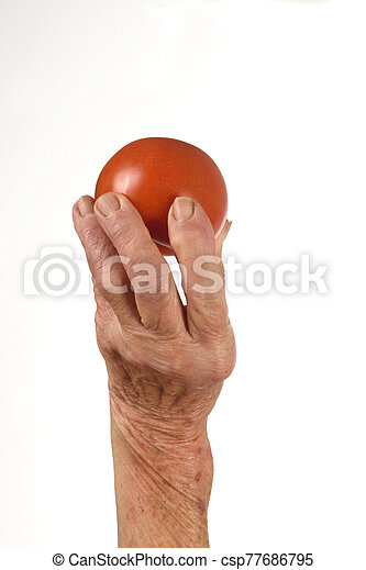 Senior woman with fruit in hand isolated on white background, tomato - csp77686795