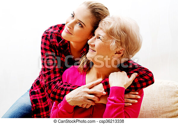 Senior woman with granddaughter or  daughter hugging on couch - csp36213338