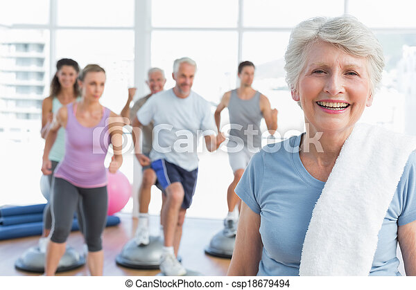 Senior woman with people exercising in fitness studio - csp18679494