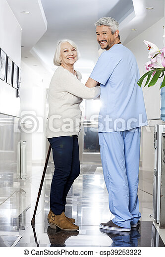 Senior Woman With Stick And Physiotherapist Standing In Rehab Ce - csp39253322