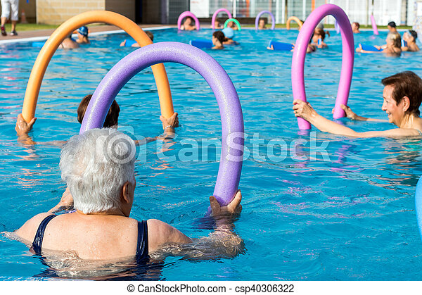 Senior women doing exercise with soft foam noodles in pool. - csp40306322