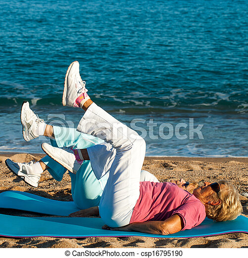 Senior women doing leg exercises on beach. - csp16795190