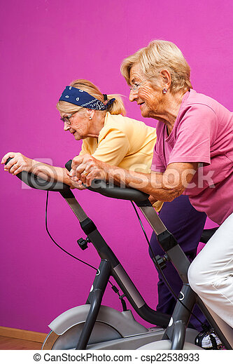 Senior women doing spinning in gym - csp22538933