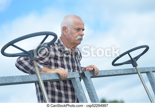 senior worker next to big valves in an industrial plant - csp52294997