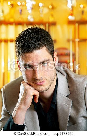 Un hombre guapo con traje sentado en billar - csp9173980