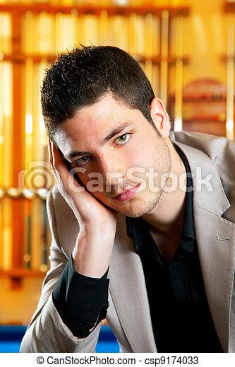 Un hombre guapo con traje sentado en billar - csp9174033