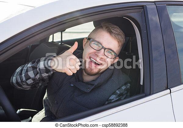 Un tipo casual alegre sonriendo alegremente mostrando los pulgares sentado en un gran coche blanco - csp58892388