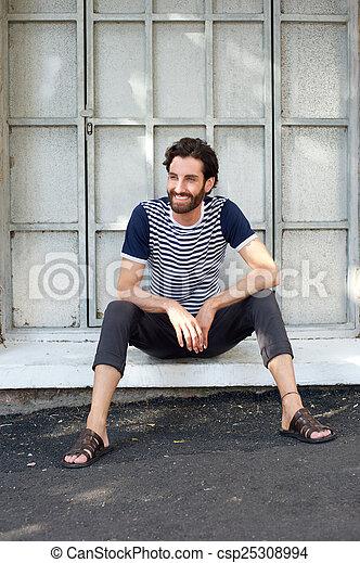 Un joven feliz sentado en el marco de una ventana - csp25308994