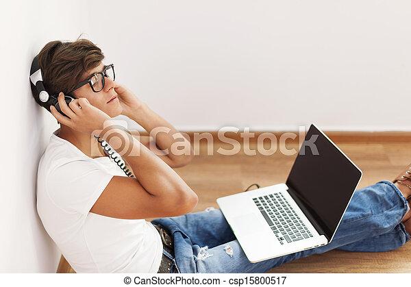 Guapo de cadera sentado contra la pared escuchando música - csp15800517