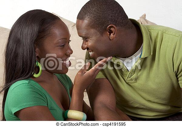 Feliz joven pareja negra étnica sentada en el sofá - csp4191595
