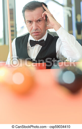 Hombre pensativo con traje posando en la piscina de billar - csp59034410