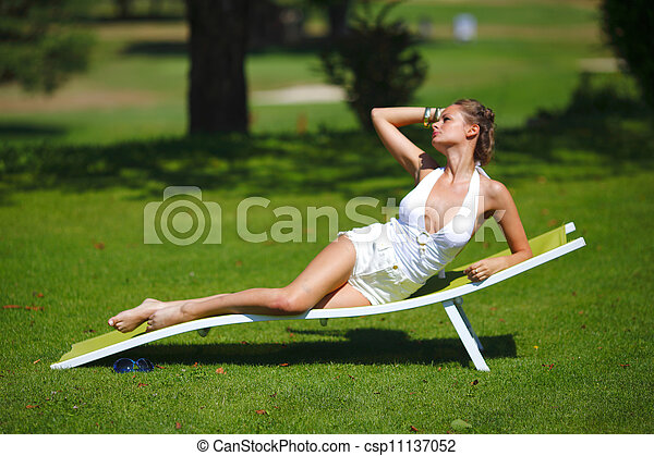 Una chica sentada en un salón blanco sobre una hierba verde - csp11137052