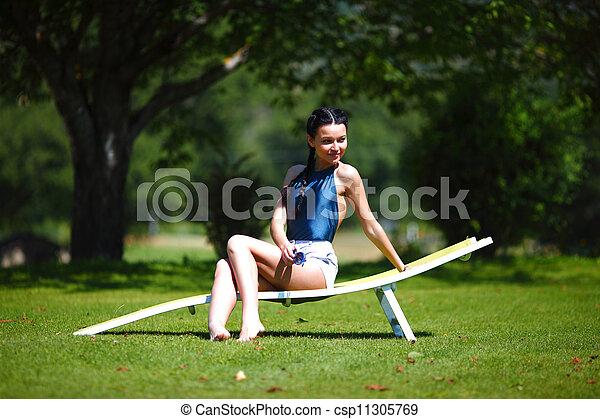 Una chica sentada en una salita blanca sobre una hierba verde - csp11305769