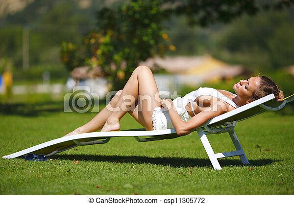 Una chica sentada en un salón blanco sobre una hierba verde - csp11305772