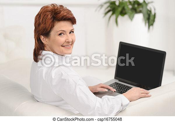 Mujer sonriente usando una laptop mientras se sienta en el sofá - csp16755048