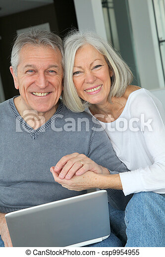 Una pareja mayor sentada en el sofá con computadora portátil - csp9954955