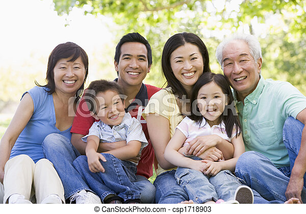 Familia extendida sentada al aire libre sonriendo - csp1718903