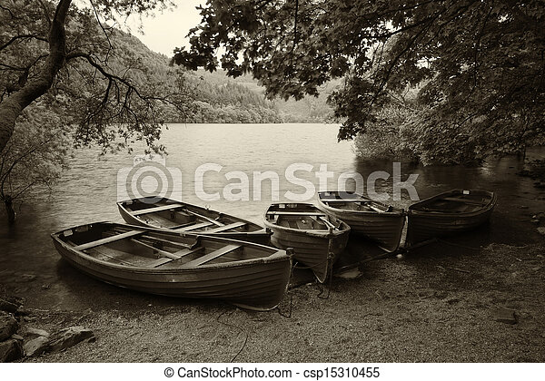 Sepia retro style picture of derelict boathouse and rowing boats landscape - csp15310455