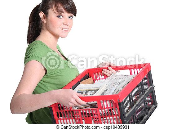 La mujer que lleva un cajón de periódicos para ser reciclada - csp10433931