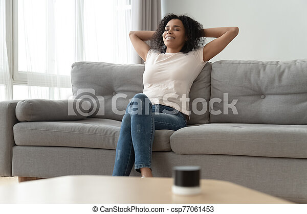 Serene african woman leaned on couch resting in living room - csp77061453
