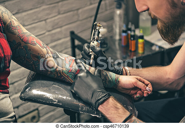 Serene bearded man creating tattoo on hand - csp46710139