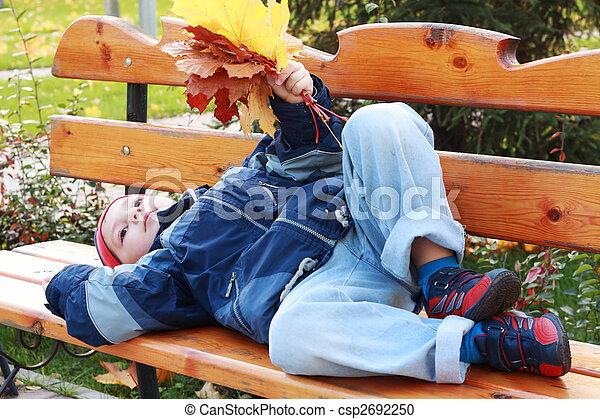 Serene boy laying on bench - csp2692250