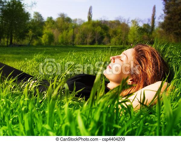 Mujer serena relajándose al aire libre con hierba fresca - csp4404209