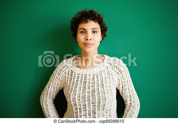 serious african american woman against green background - csp69399010
