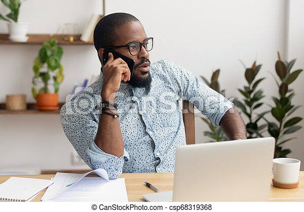 Serious african businessman talking on phone sitting at office desk - csp68319368