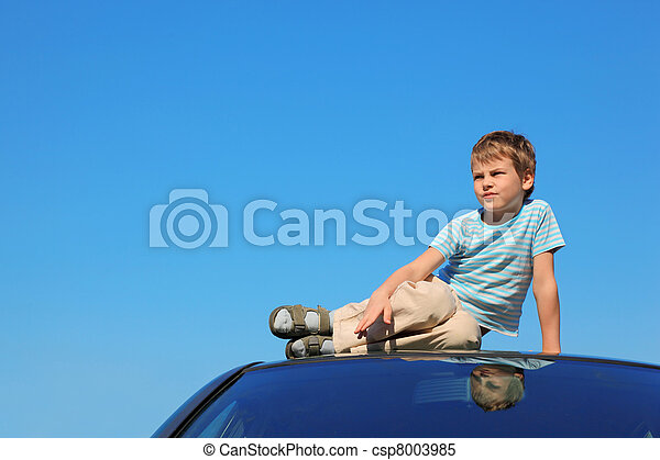 serious boy sitting on roof of car, blue sky - csp8003985