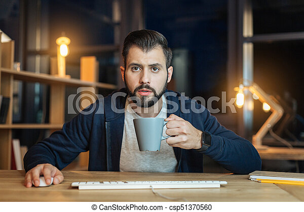 Serious brunette going to drink coffee - csp51370560