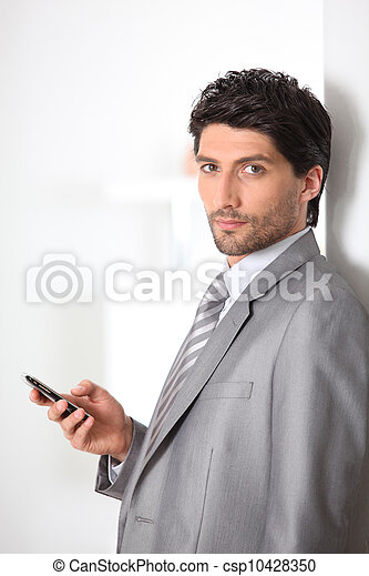Serious businessman holding a mobile phone - csp10428350