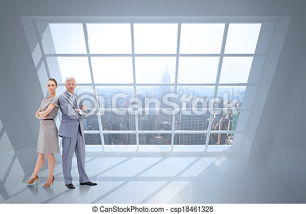 Serious businessman standing back to back with a woman against room with large window showing city - csp18461328