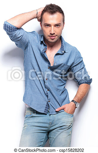 serious casual man poses with hand on head and in pocket