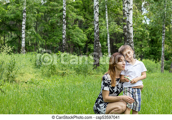 Serious little boy talking with his mother in the city park on a summer sunny day - csp53597041
