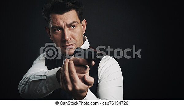 Serious man is holding a gun over black background - csp76134726