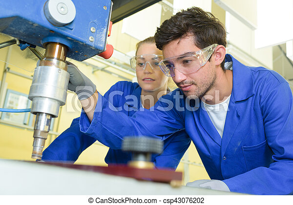 serious trainees focused on drilling metal piece with professional machinery - csp43076202