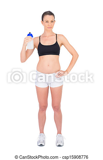 Serious woman in sportswear holding flask - csp15908776