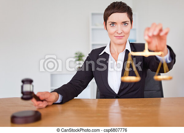 Serious woman with a gavel and the justice scale - csp6807776