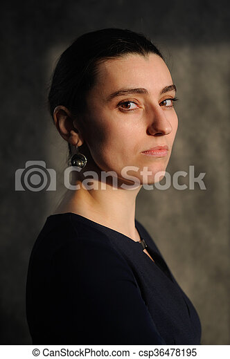 Serious young brunette woman in black dress on dark background - csp36478195