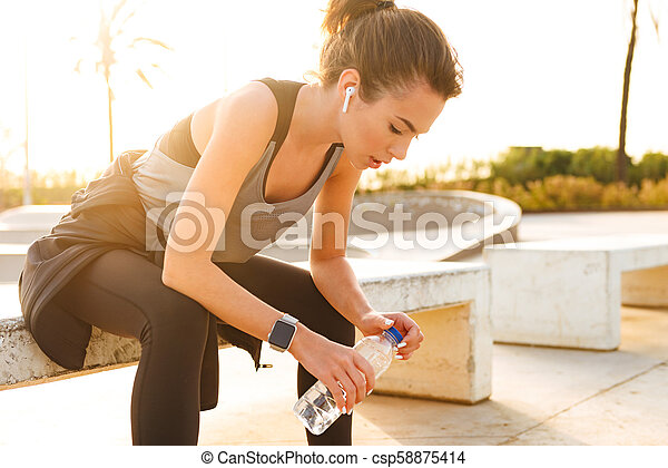 Serious young sports woman sitting outdoors - csp58875414