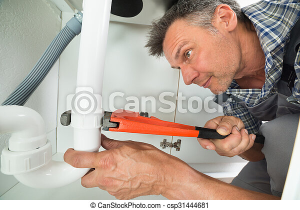 Serviceman fixing sink pipe in kitchen. Cropped image of... pictures ...