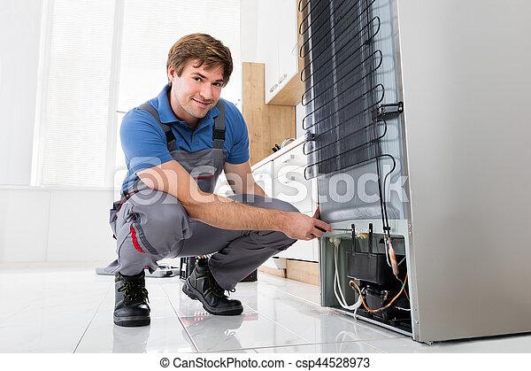 Serviceman Working On Fridge With Screwdriver - csp44528973