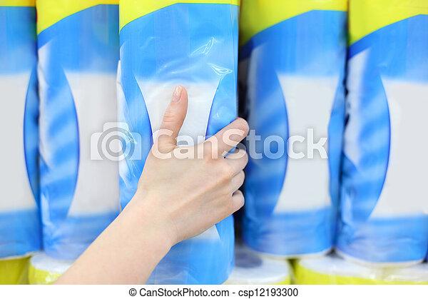 La mano de la mujer toma un gran paquete de papel higiénico en la tienda, profundidad superficial del campo - csp12193300