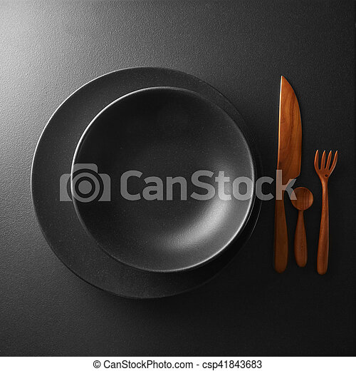 serving of black table with dark wooden utensils and cutlery - csp41843683