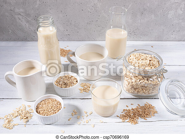 Set of different containers with oat milk, oat seeds and flakes on white wooden table on concrete background. - csp70696169